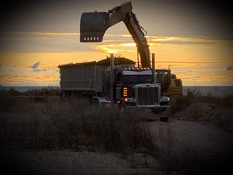 collecting dry bulk in end dump trailer bed at sunset